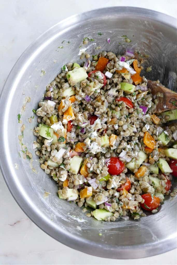 Greek lentil salad ingredients mixed together with a wooden spoon in a serving bowl