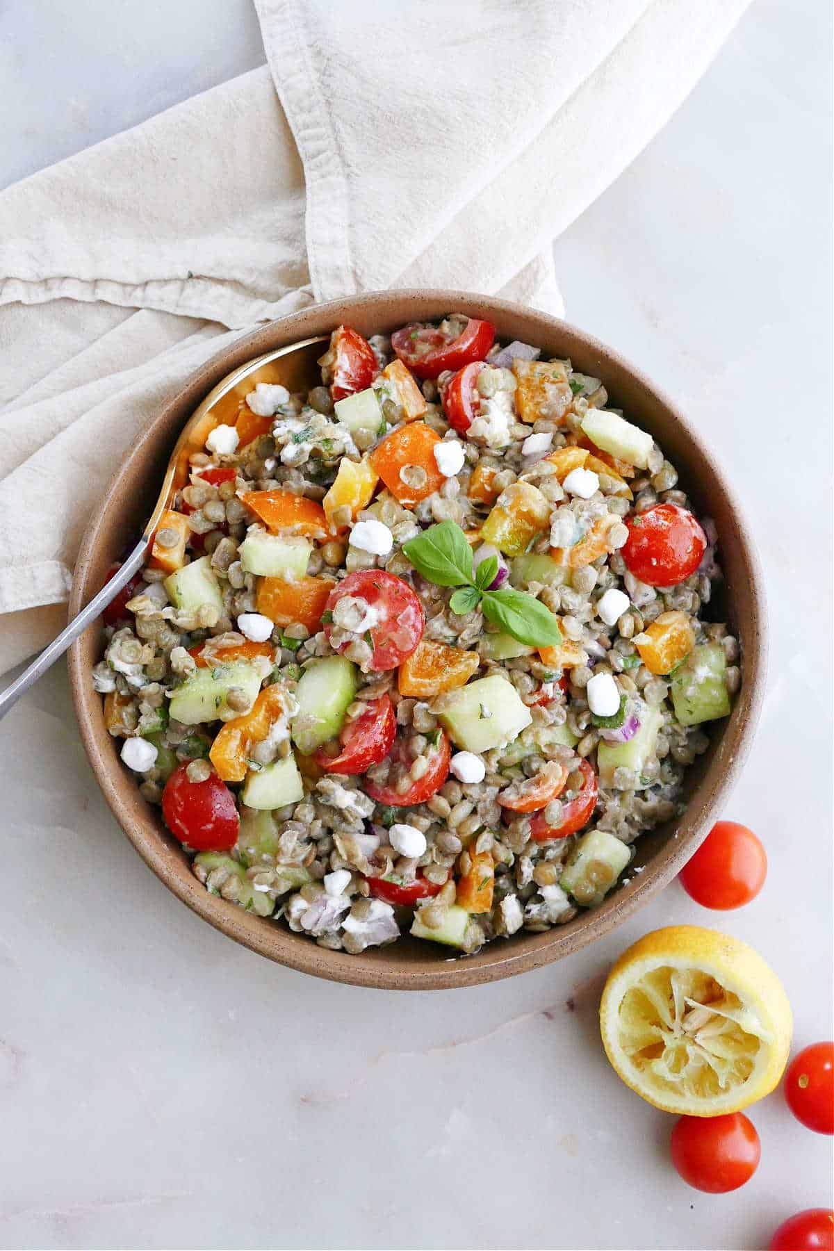 Greek lentil salad in a serving bowl next to tomatoes, lemon, and a napkin
