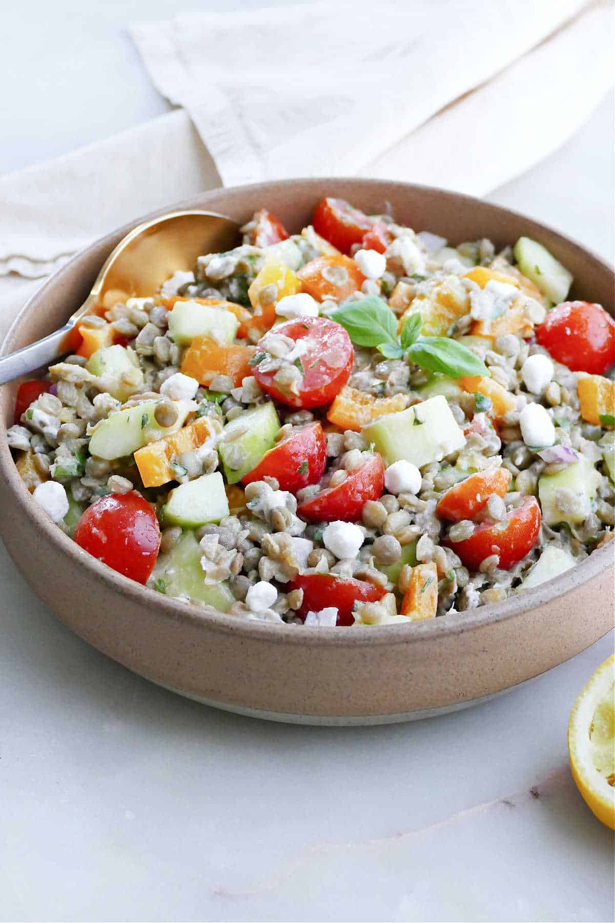 Greek lentil salad topped with basil in a bowl with a golden spoon