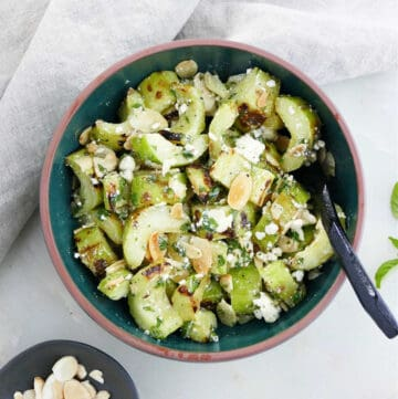 grilled cucumber with feta and mint in a serving bowl with a spoon on a counter