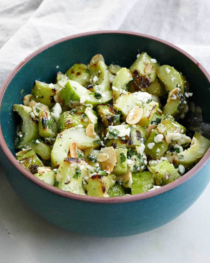 grilled cucumber salad with feta, mint, and almonds in a serving bowl