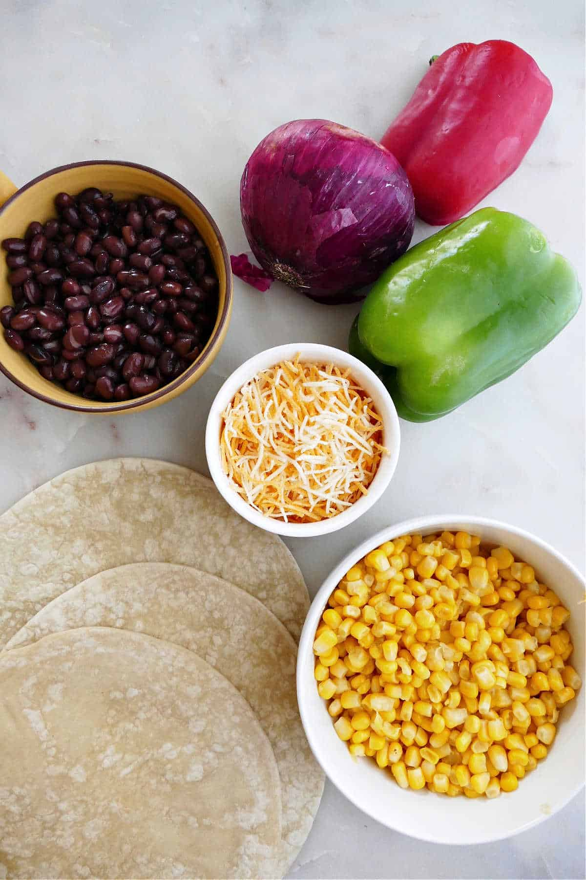 black beans, peppers, red onion, corn, cheese, and tortillas spread out on a counter
