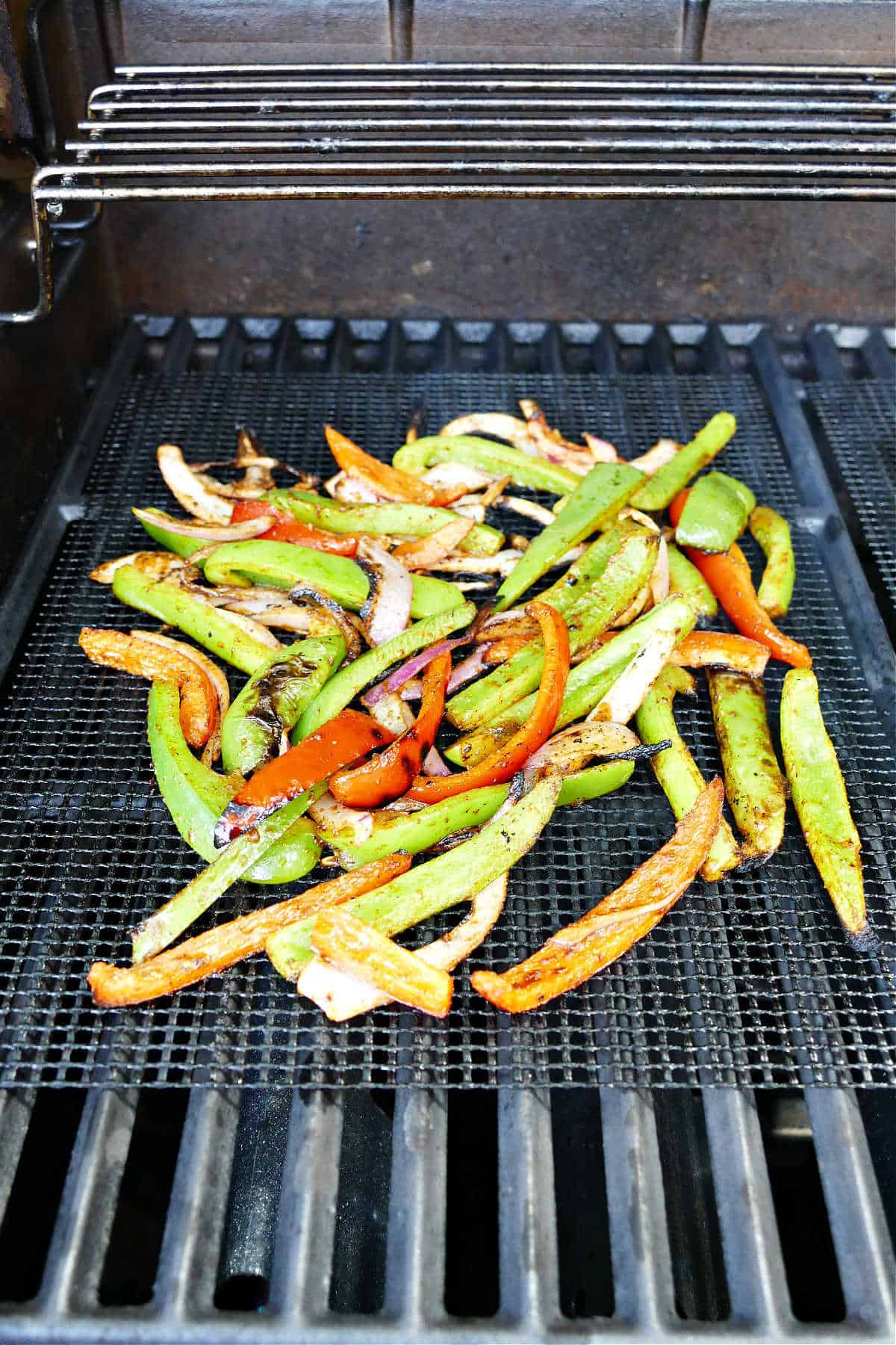 sliced peppers and onions cooking on a mesh mat over a grill