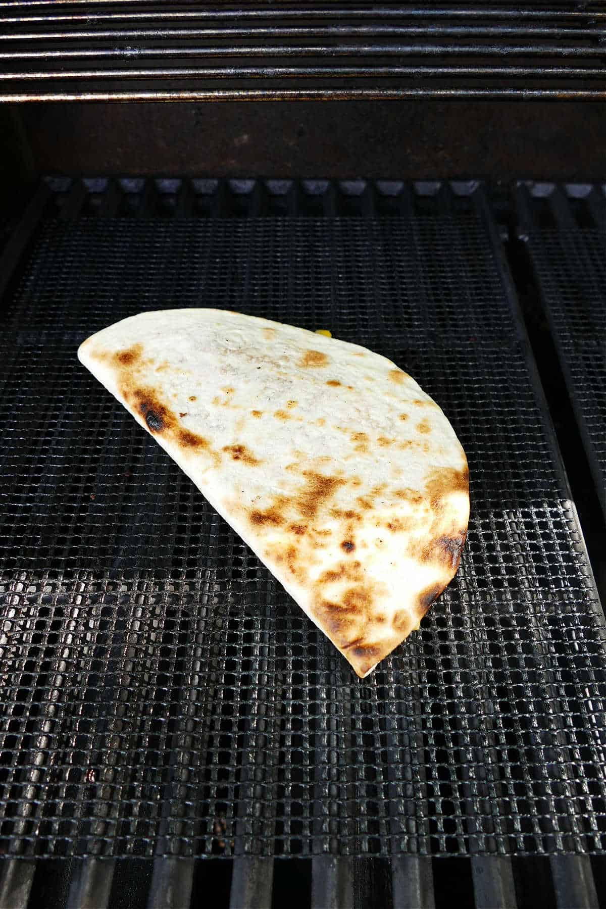 a cheese and veggie quesadilla cooking on a mesh mat over a grill