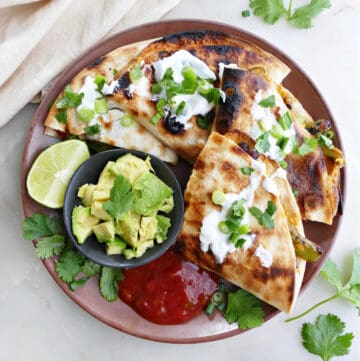grilled quesadilla sliced into four pieces on a plate with salsa, avocado, and lime