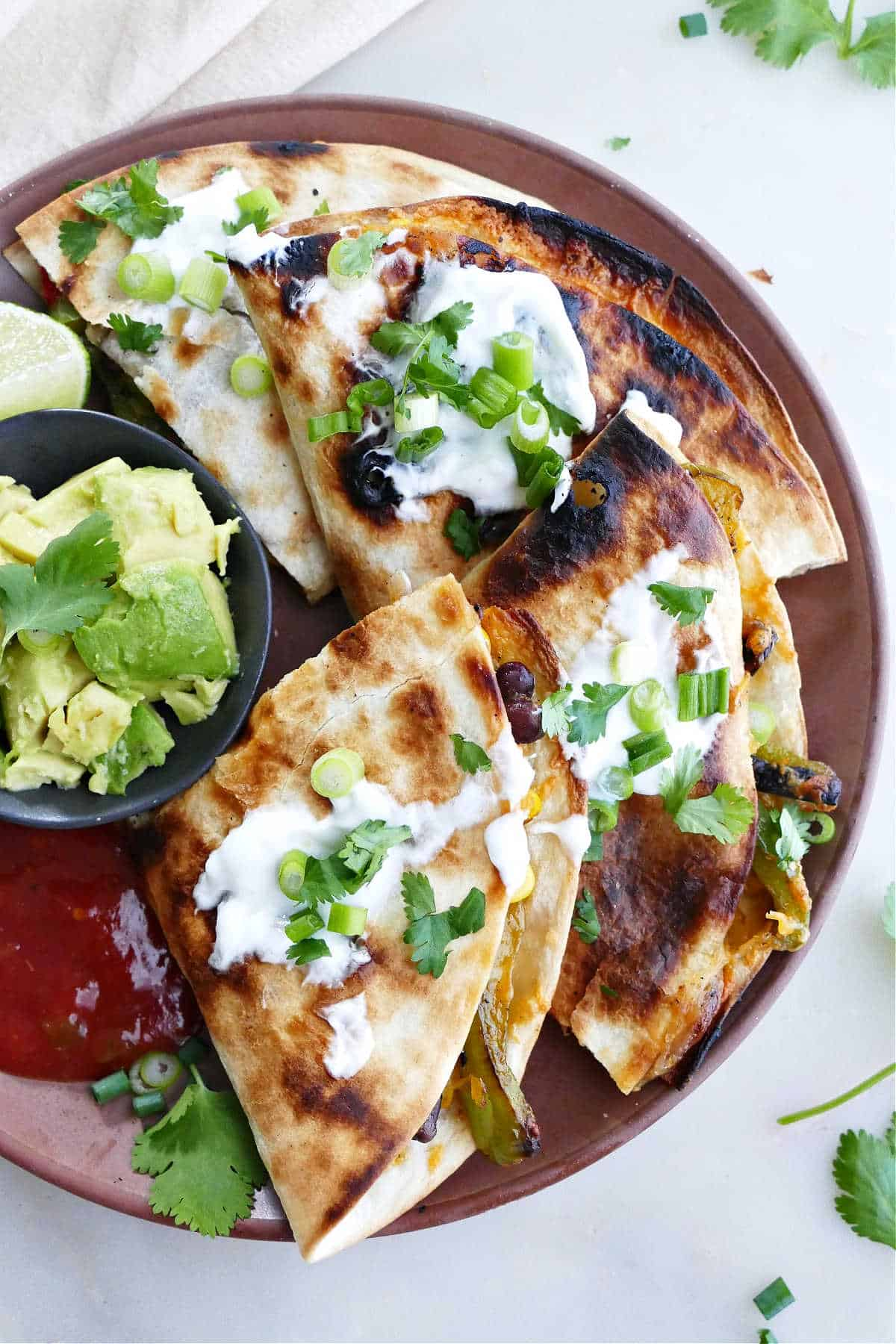 grilled quesadilla sliced into pieces on a serving plate topped with cilantro