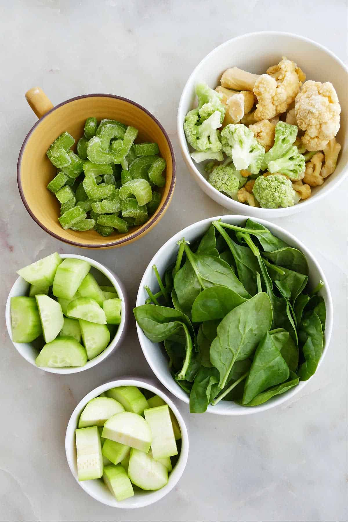 celery, cauliflower, spinach, cucumber, and zucchini in bowls spread out on a counter