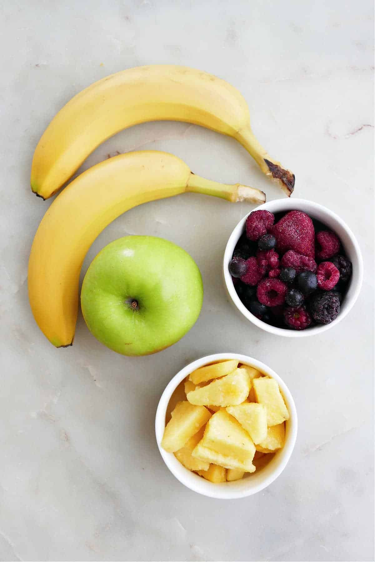 bananas, green apple, berries, and pineapple in bowls spread out on a counter
