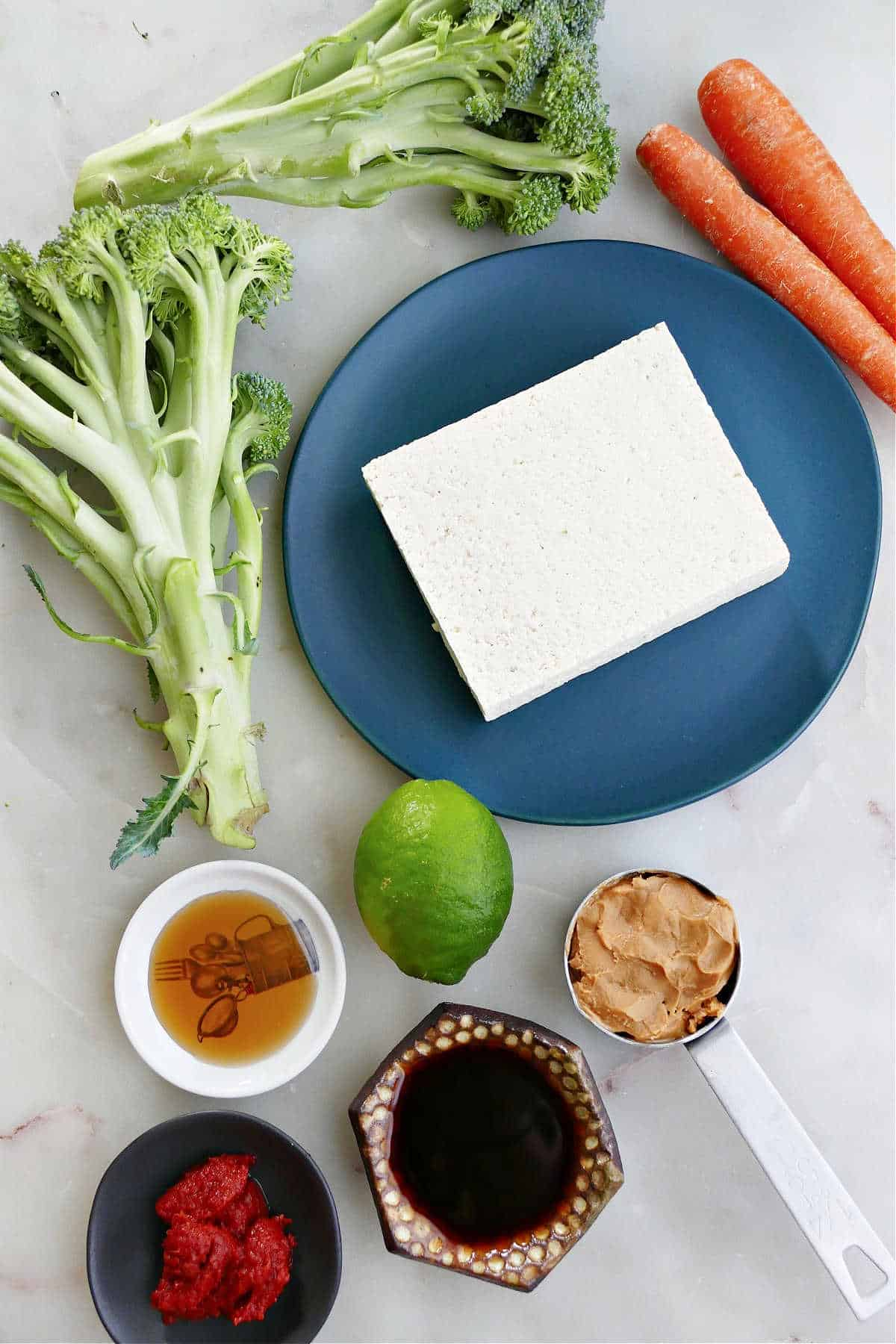 broccoli, tofu, carrots, lime, and peanut sauce ingredients next to each other on a counter