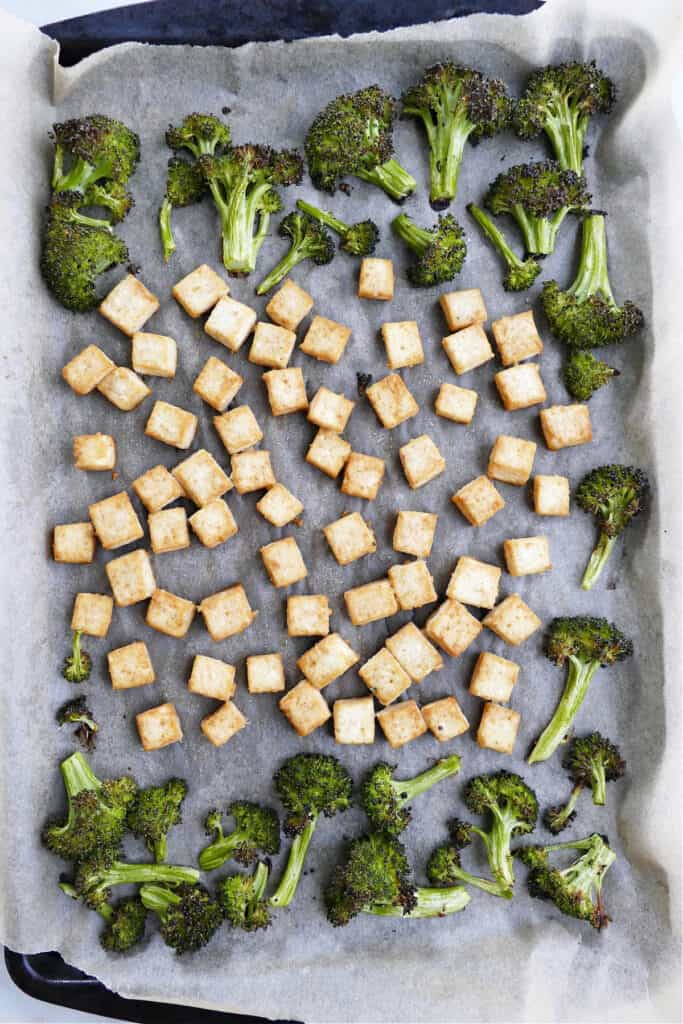 roasted broccoli florets and tofu cubes on a lined baking sheet