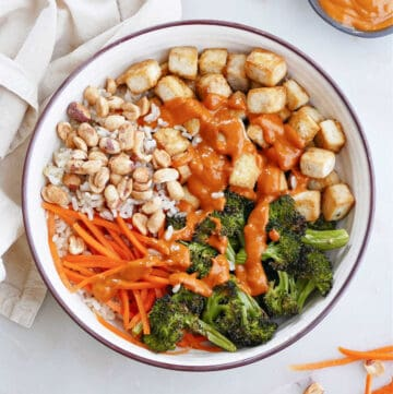 spicy peanut tofu buddha bowl on a counter surrounded by ingredients