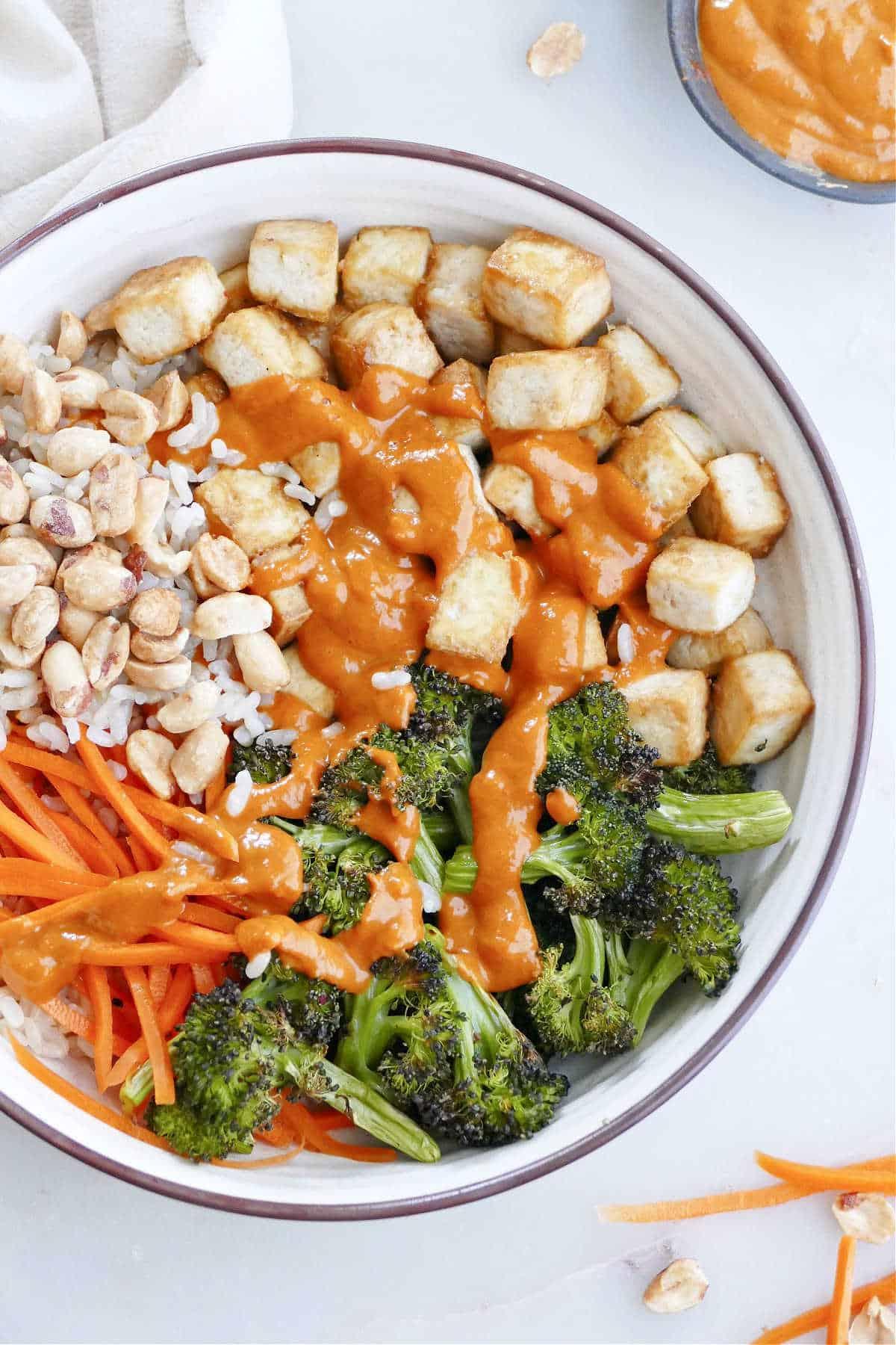 tofu buddha bowl with peanut sauce, rice, and veggies on a counter
