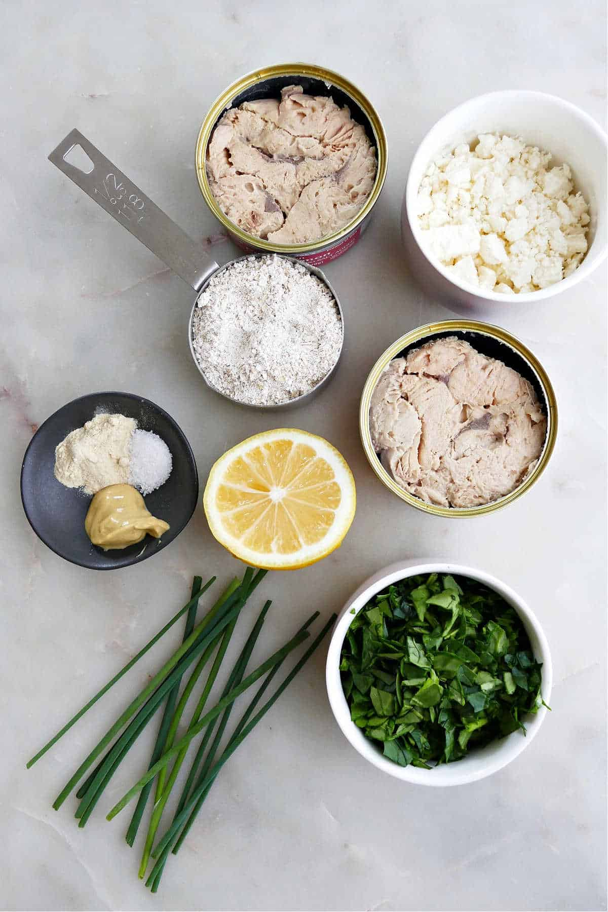 canned salmon, feta cheese, ground oats, lemon, seasonings, and spinach on a counter