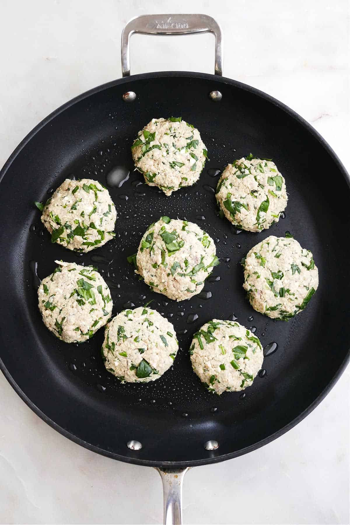 eight salmon burgers cooking in a large black skillet on a counter
