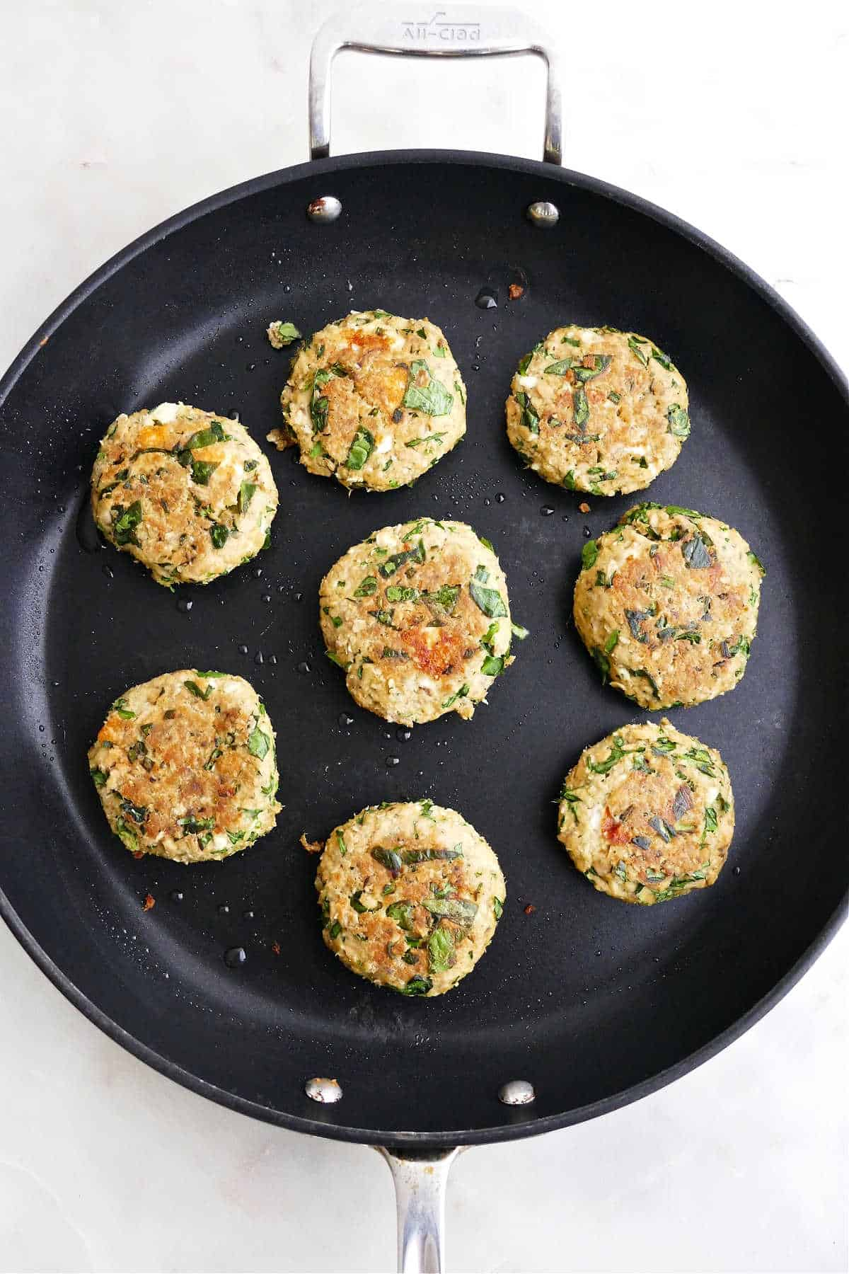 eight cooked spinach feta salmon burgers in a large black skillet on a counter