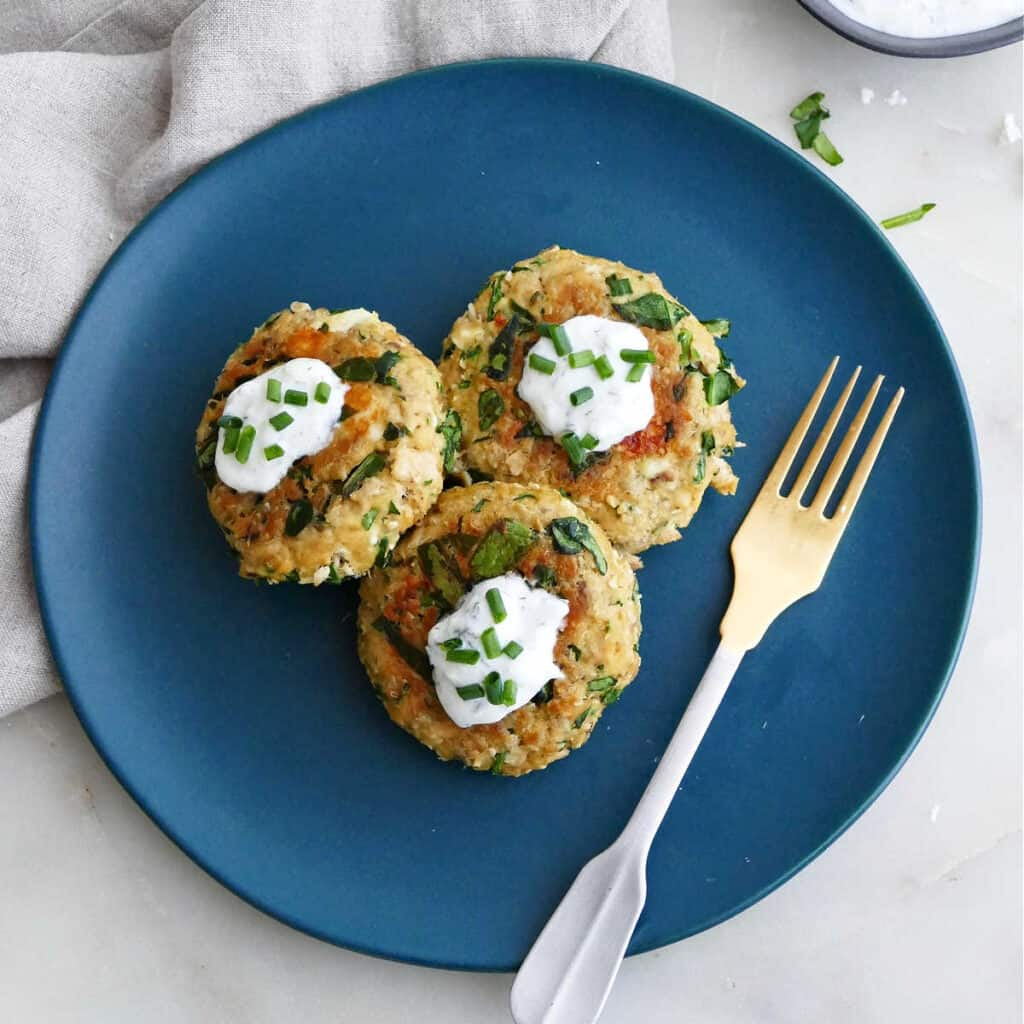 three spinach feta salmon burgers on a serving plate topped with yogurt and chives