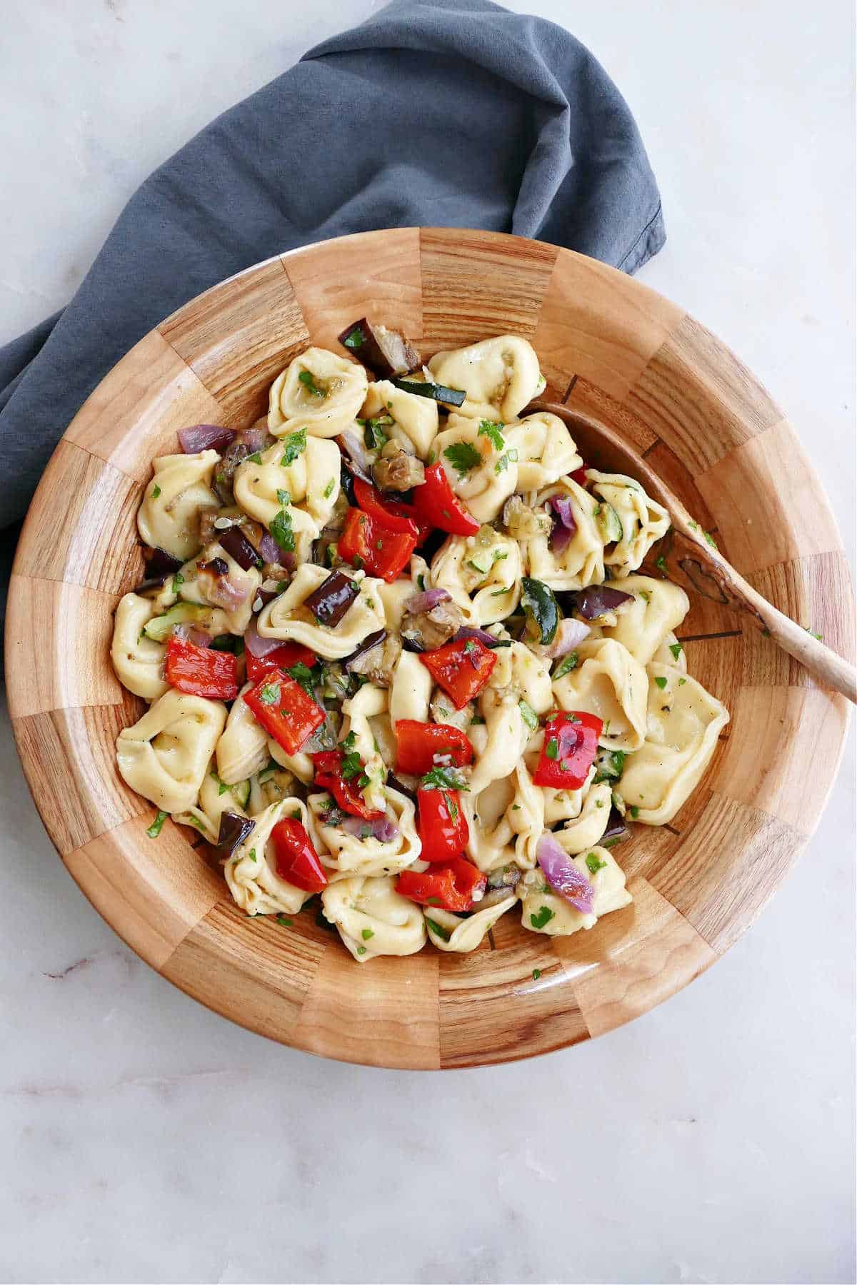 summer tortellini salad in a serving bowl next to napkin on a counter