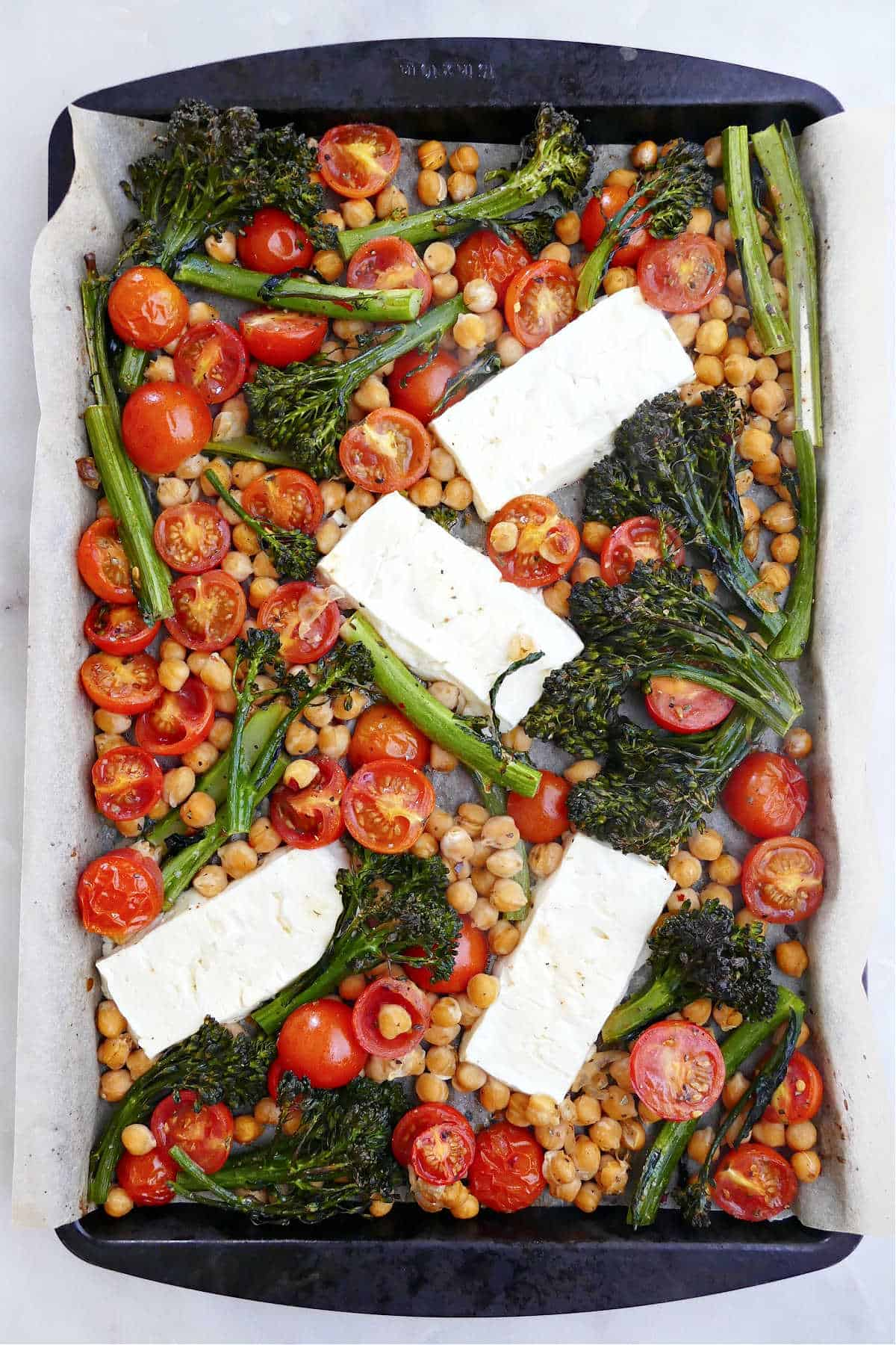 feta, vegetables, and chickpeas spread out on a baking sheet lined with parchment paper