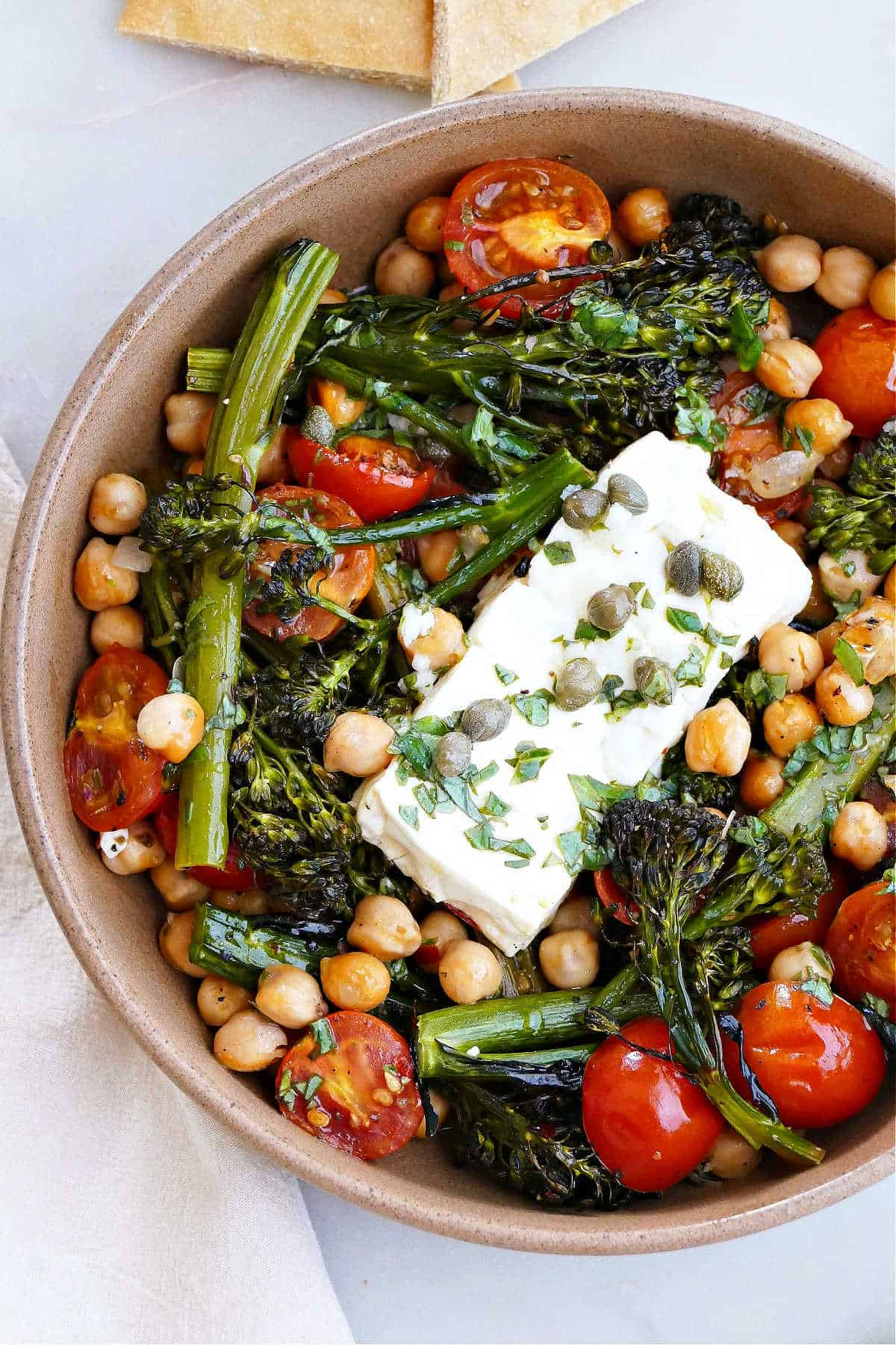 baked feta with vegetables and chickpeas in a serving bowl on a counter