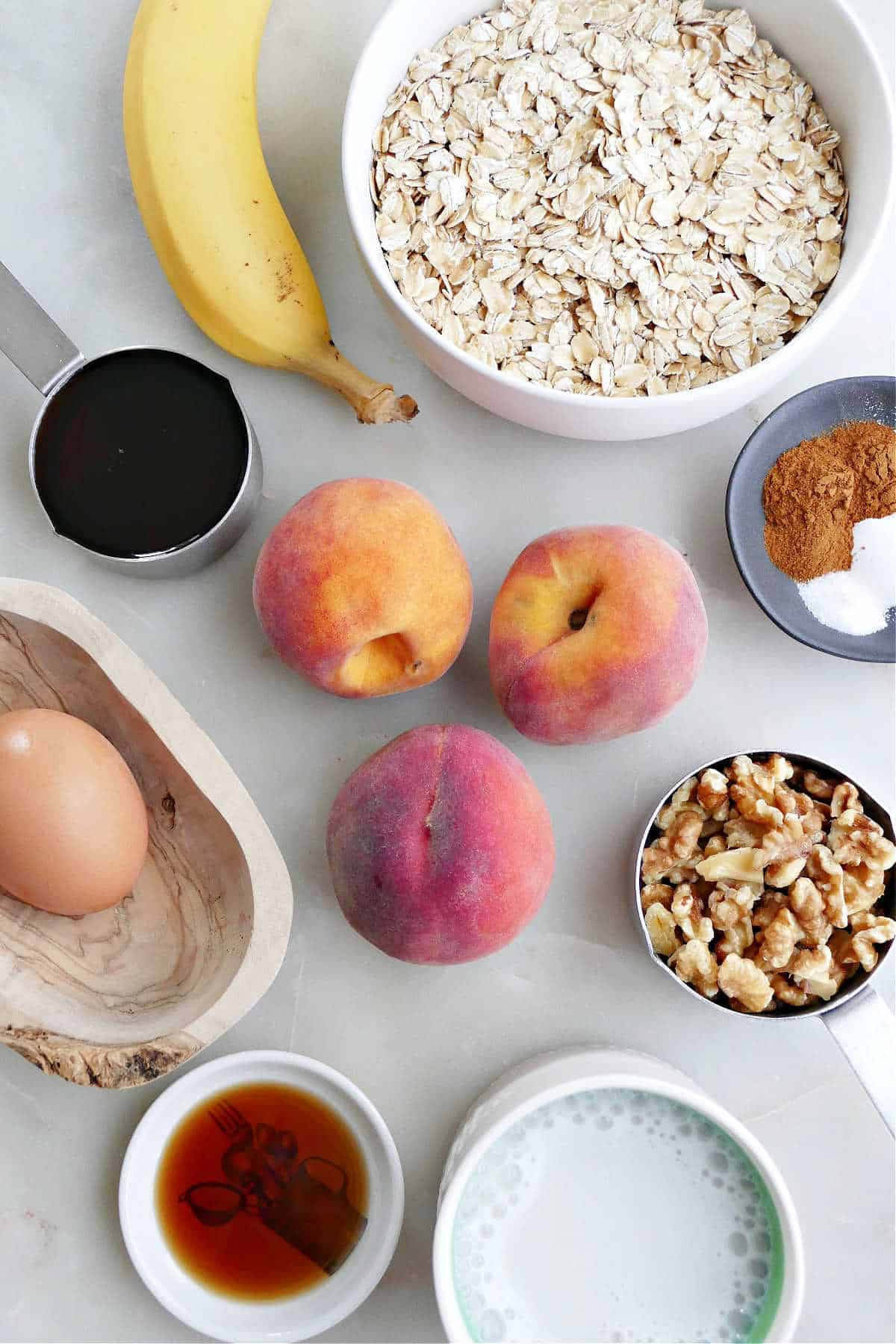 banana, peaches, oats, spices, walnuts, maple syrup, egg, vanilla, and milk on a counter