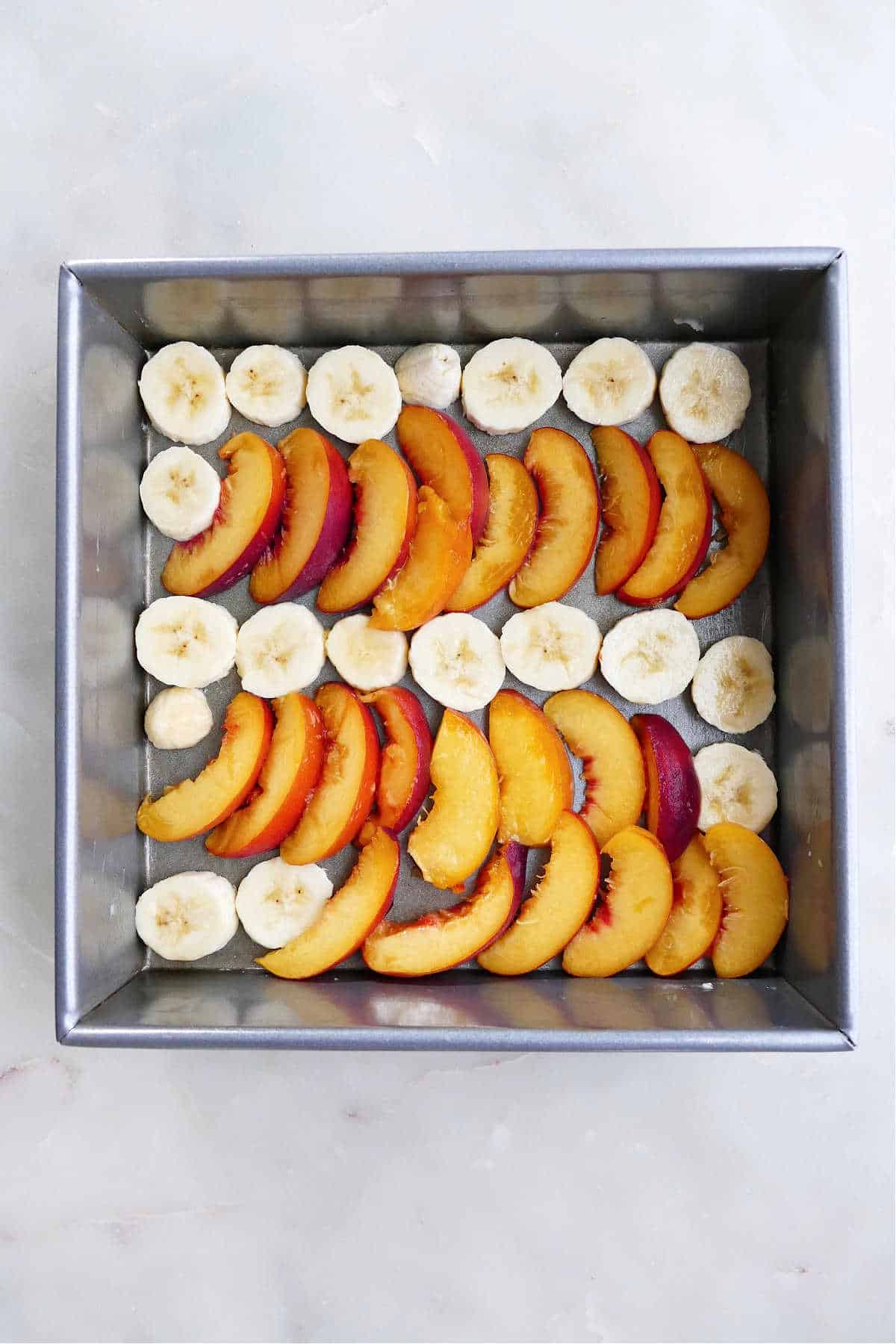 sliced bananas and sliced peaches spread out on a greased baking dish