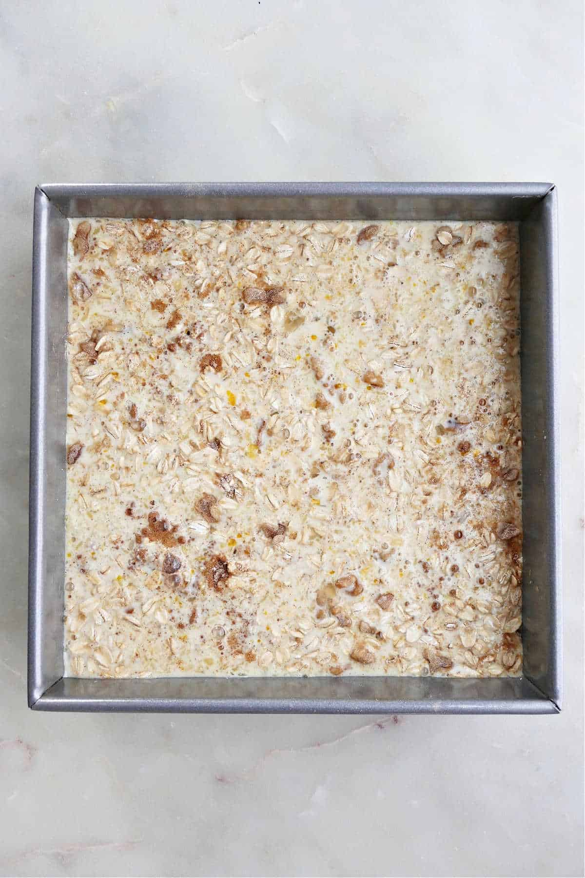 dry and wet ingredients for baked peach oatmeal spread out in a baking dish