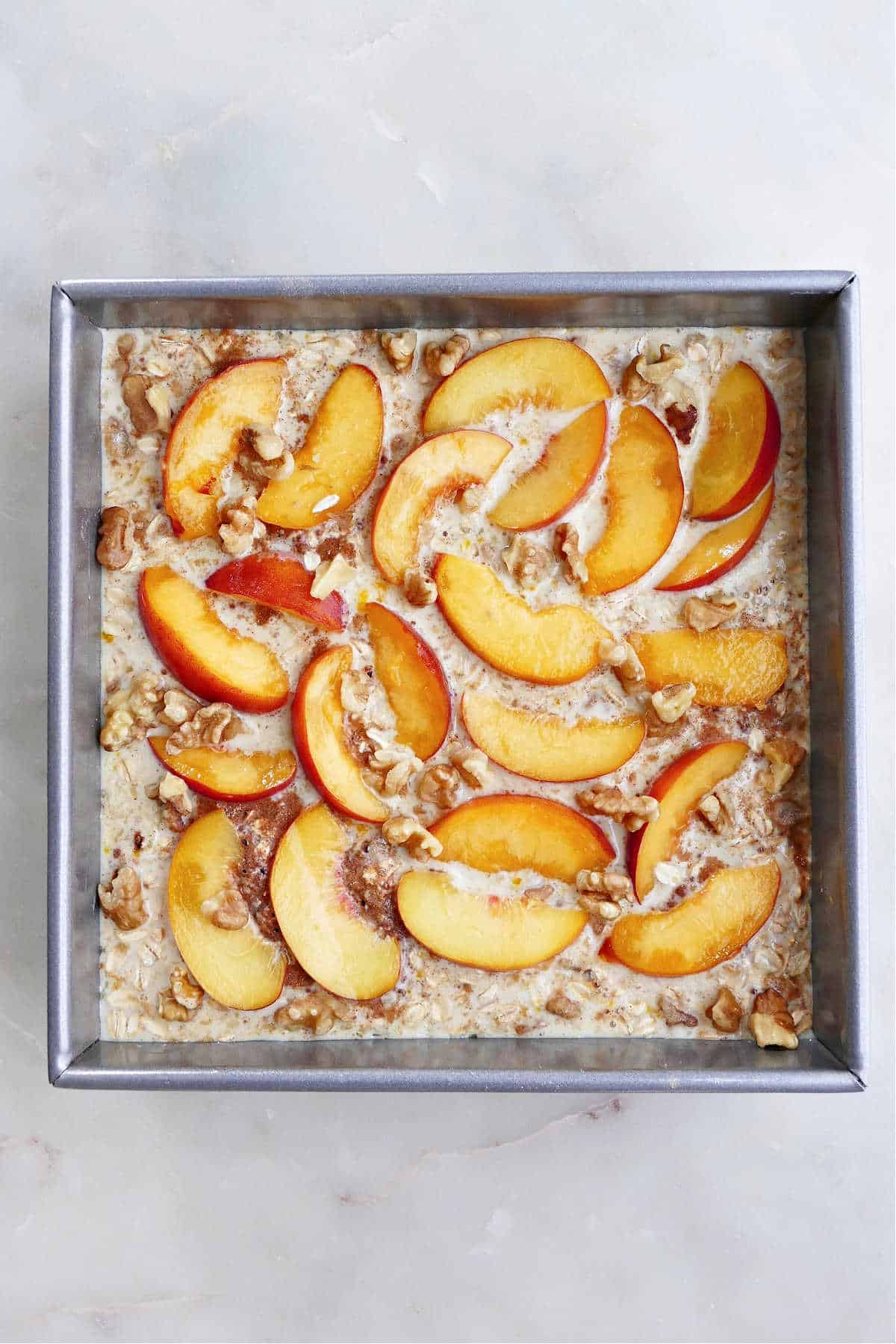 peach oatmeal before going into the oven in a baking dish on a counter