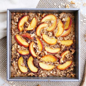 baked peach oatmeal in a square baking dish on a placemat next to a napkin