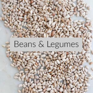 dried pinto beans on a counter with text box in the middle labeled with beans and legumes