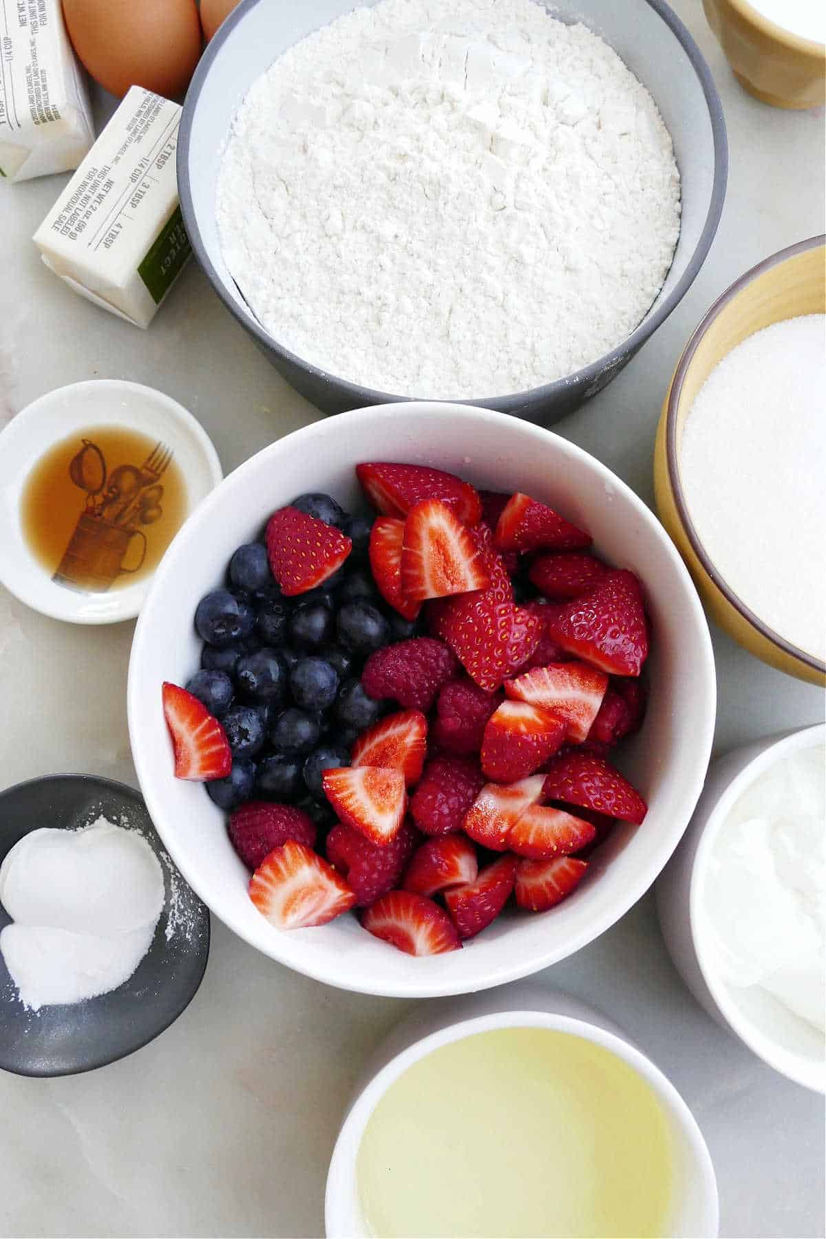 ingredients for berry cupcakes spread out next to each other on a counter