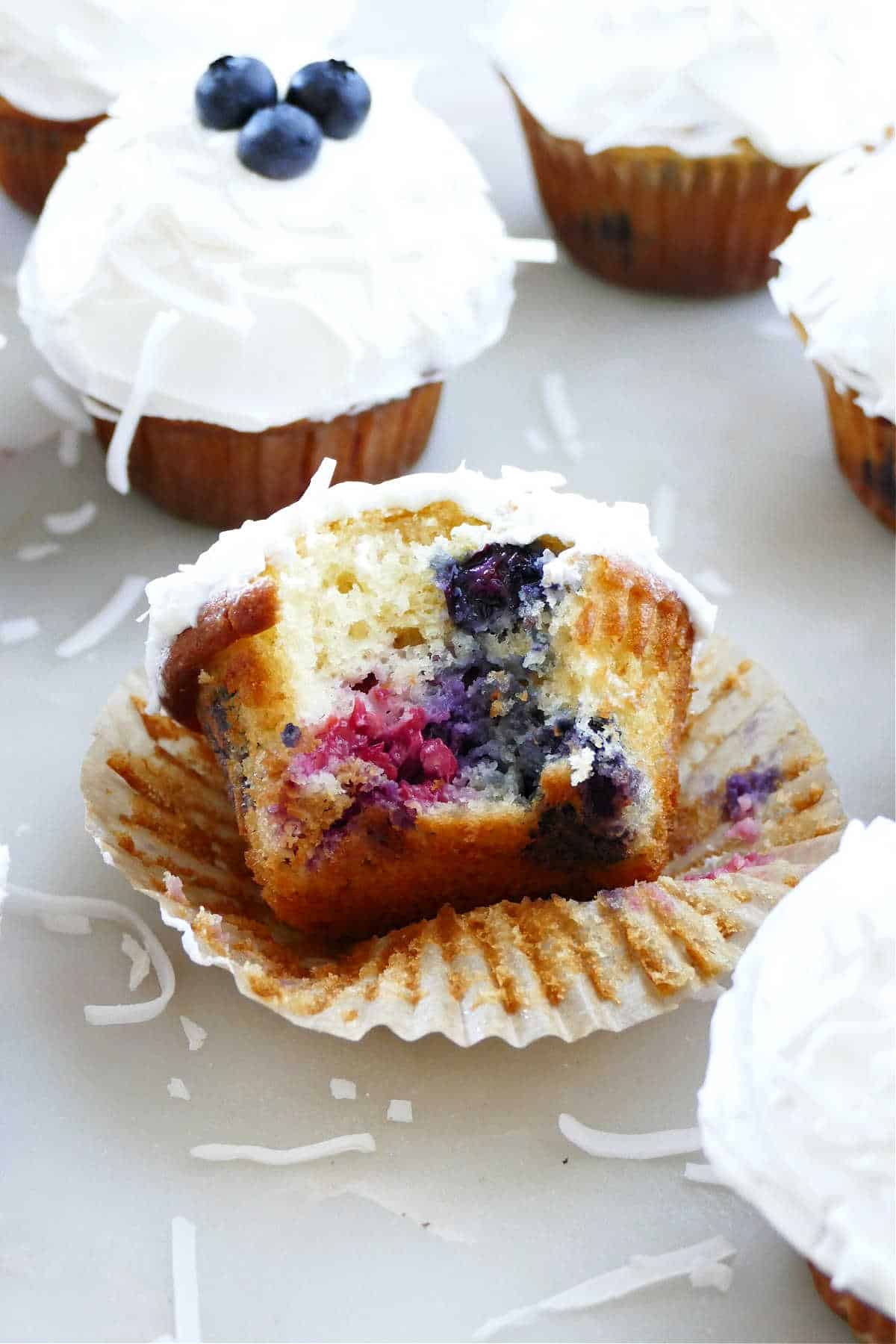 a triple berry cupcake with a bite taken out on a cupcake liner on a counter