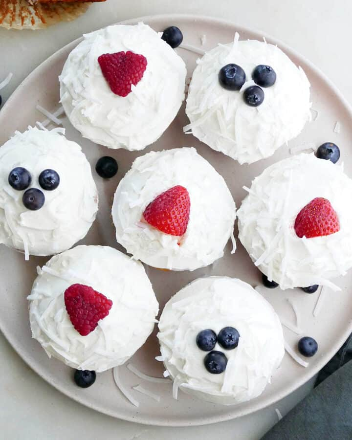 seven berry cupcakes on a circular serving platter next to a sliced cupcake and napkin