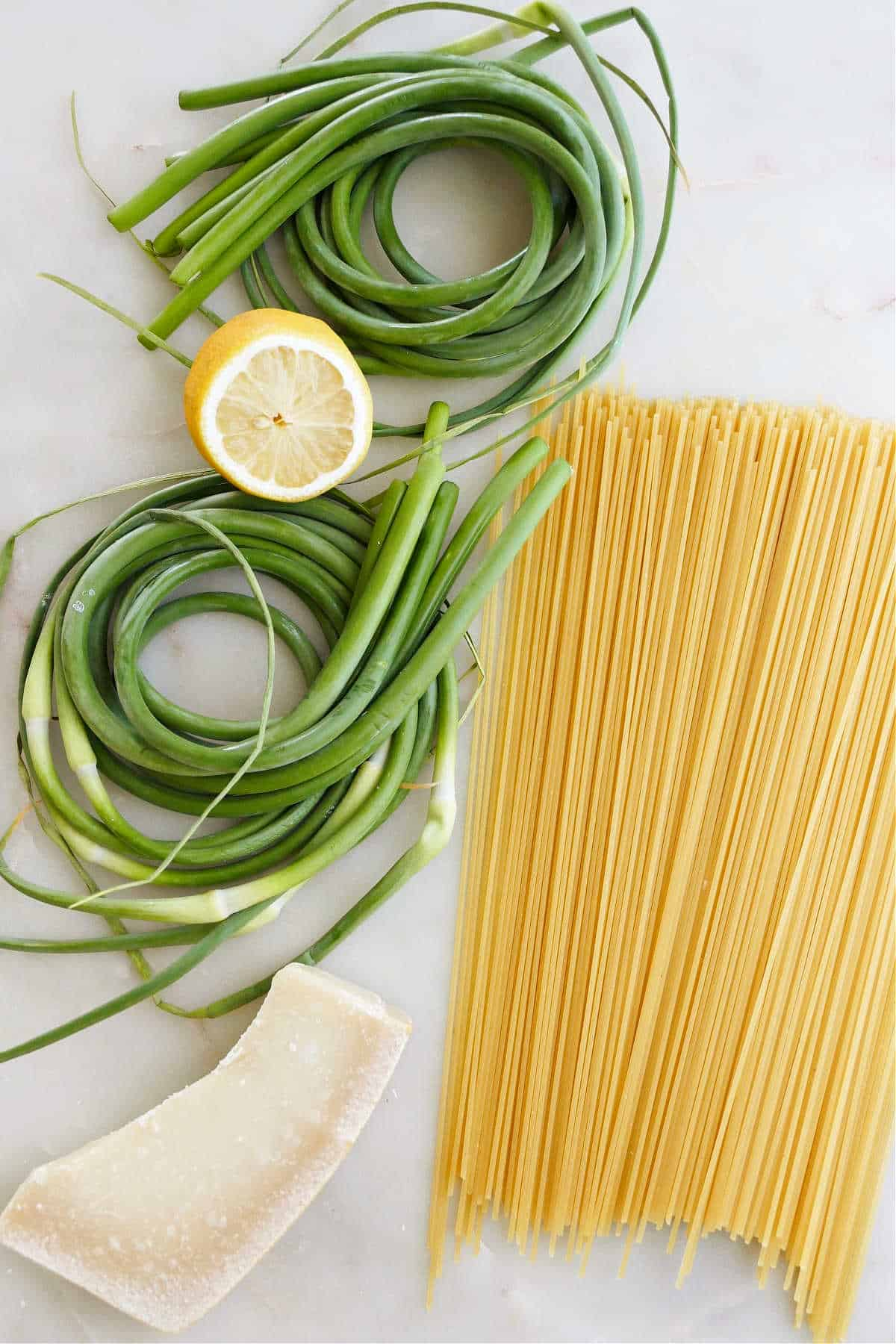 garlic scapes, lemon, spaghetti, and parmesan spread out next to each other on a counter