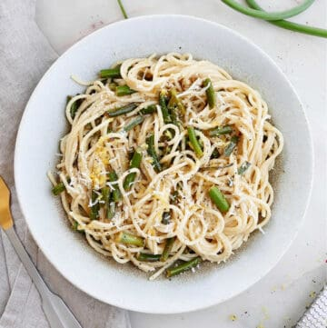 garlic scape pasta topped with lemon zest and cheese in a serving bowl