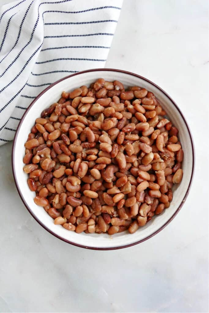 Instant Pot pinto beans in a serving bowl on a counter next to a striped napkin