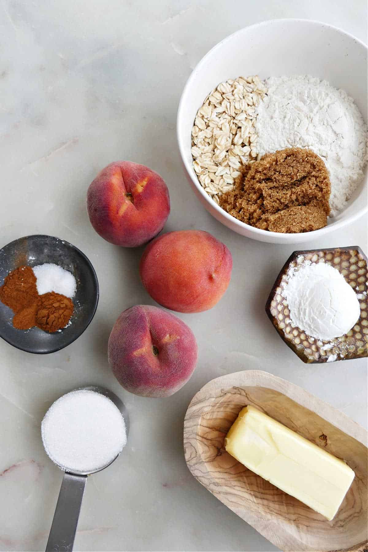 peaches, oats, flour, spices, sugar, butter, and cornstarch spread out on a counter