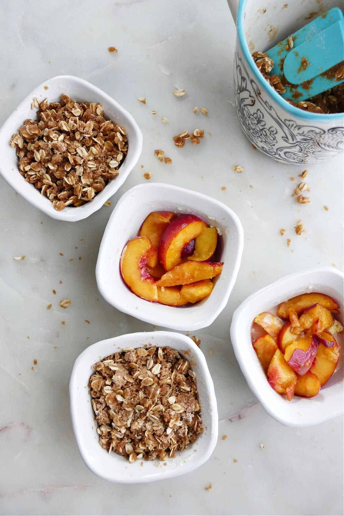 four individual peach crisps next to each other on a counter being prepared to bake