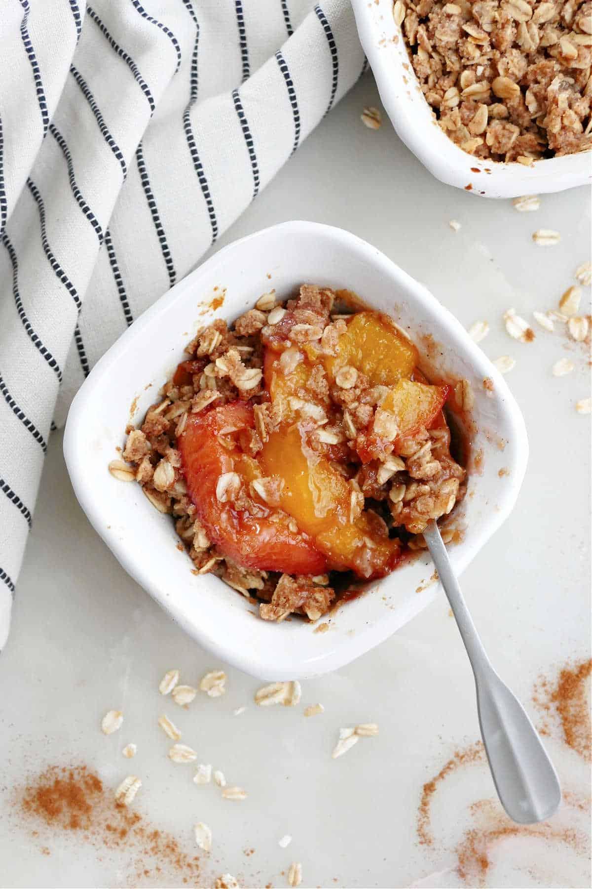 mini peach cobbler in a ramekin with a small spoon next to a napkin