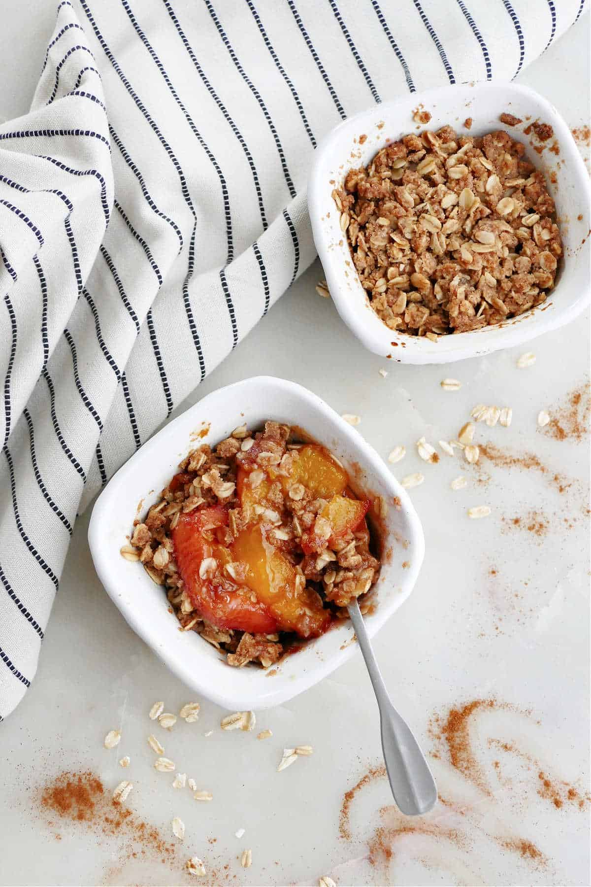 two mini peach cobblers in ramekins on a counter next to a striped napkin