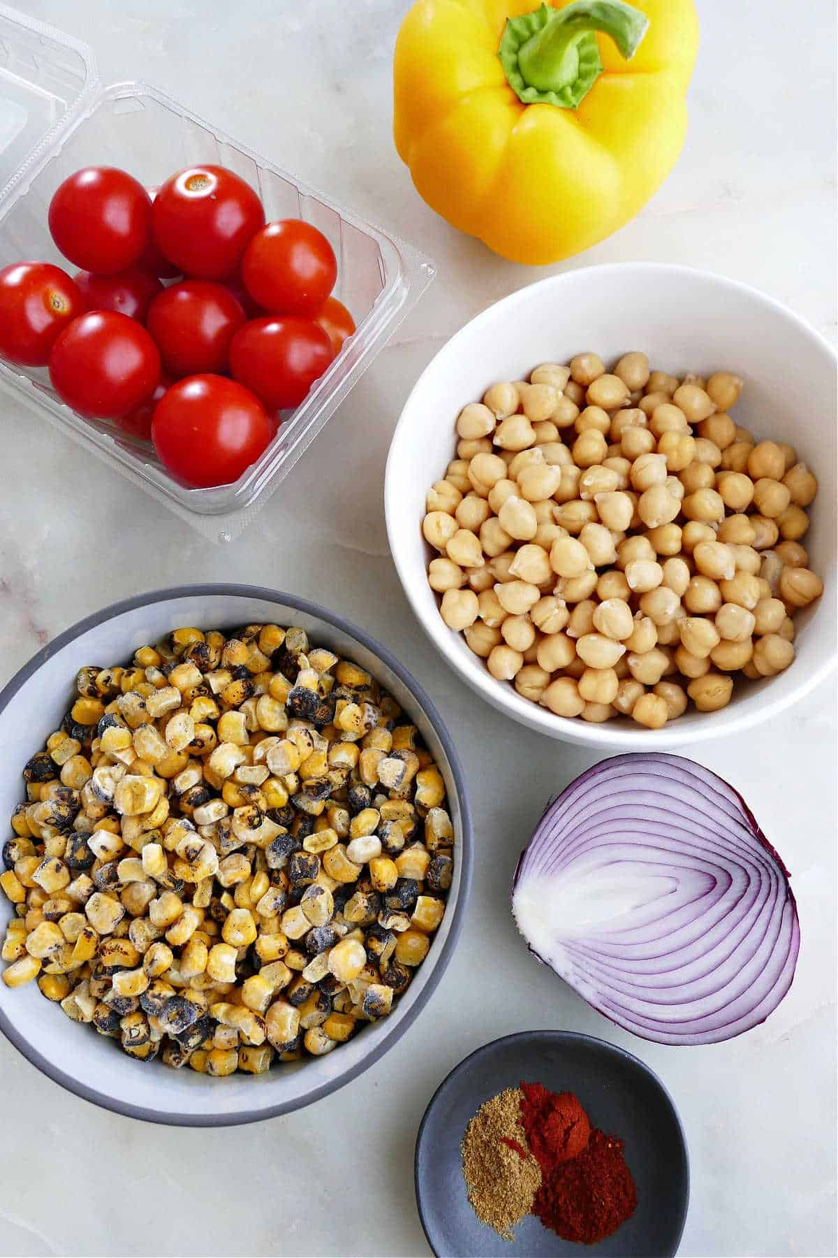 bell pepper, tomatoes, chickpeas, charred corn, red onion, and spices on a counter