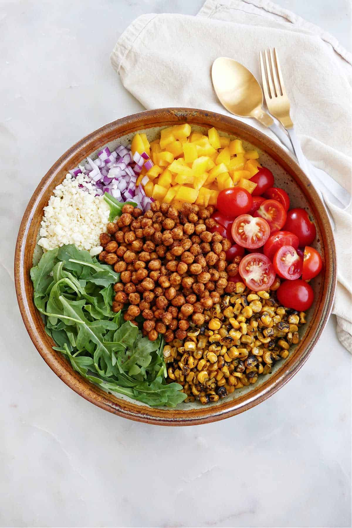 arugula, roasted chickpeas, corn, tomatoes, pepper, onion, and cheese in a large serving bowl