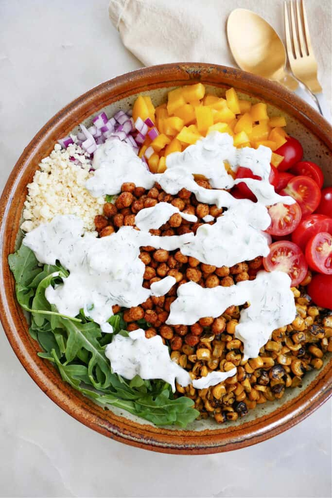 ingredients for roasted chickpea salad with yogurt dressing drizzled on top in a bowl