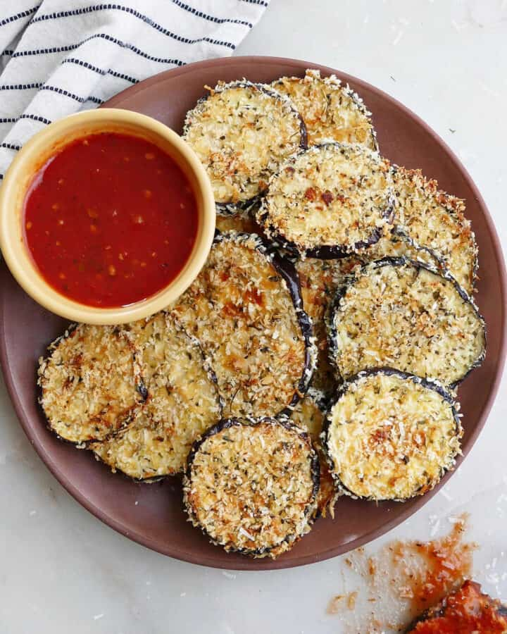 crispy baked eggplant slices on a serving dish with marinara sauce next to a striped napkin