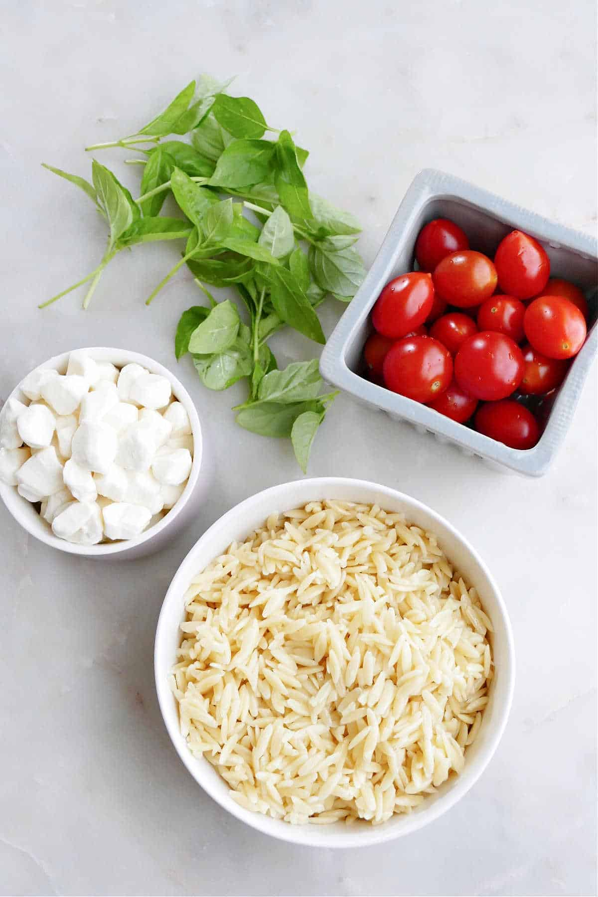 orzo pasta, mozzarella pearls, cherry tomatoes, and basil leaves on a counter