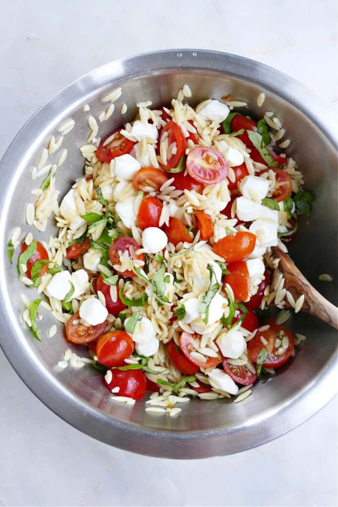 ingredients for caprese orzo salad in a bowl being mixed with a spoon