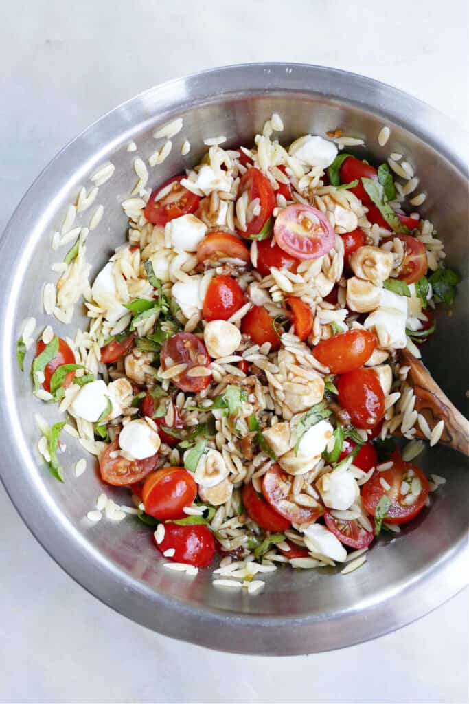 caprese orzo salad mixed together in a bowl and drizzled with balsamic vinaigrette