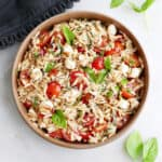 caprese orzo salad in a serving dish next to basil and a napkin