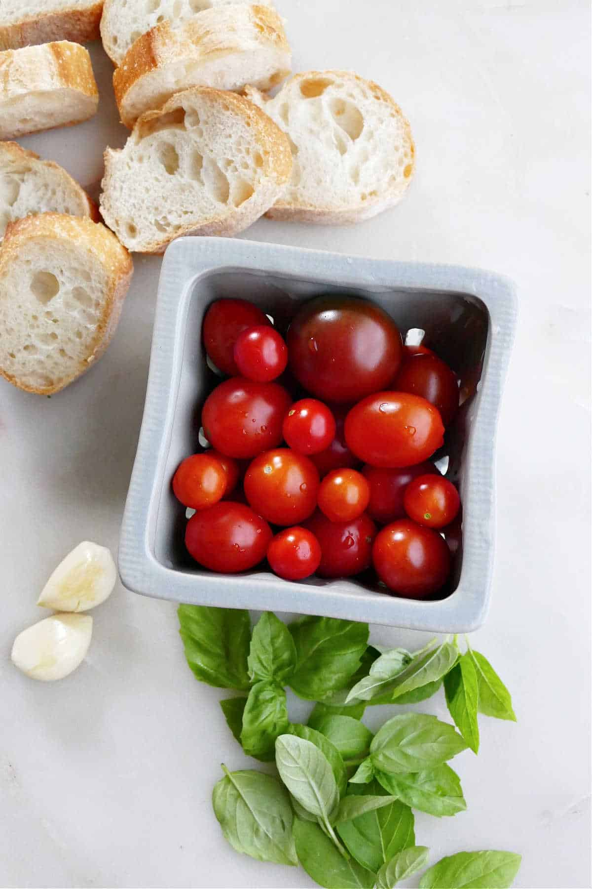 baguette slices, cherry tomatoes, garlic, and basil next to each other on a counter