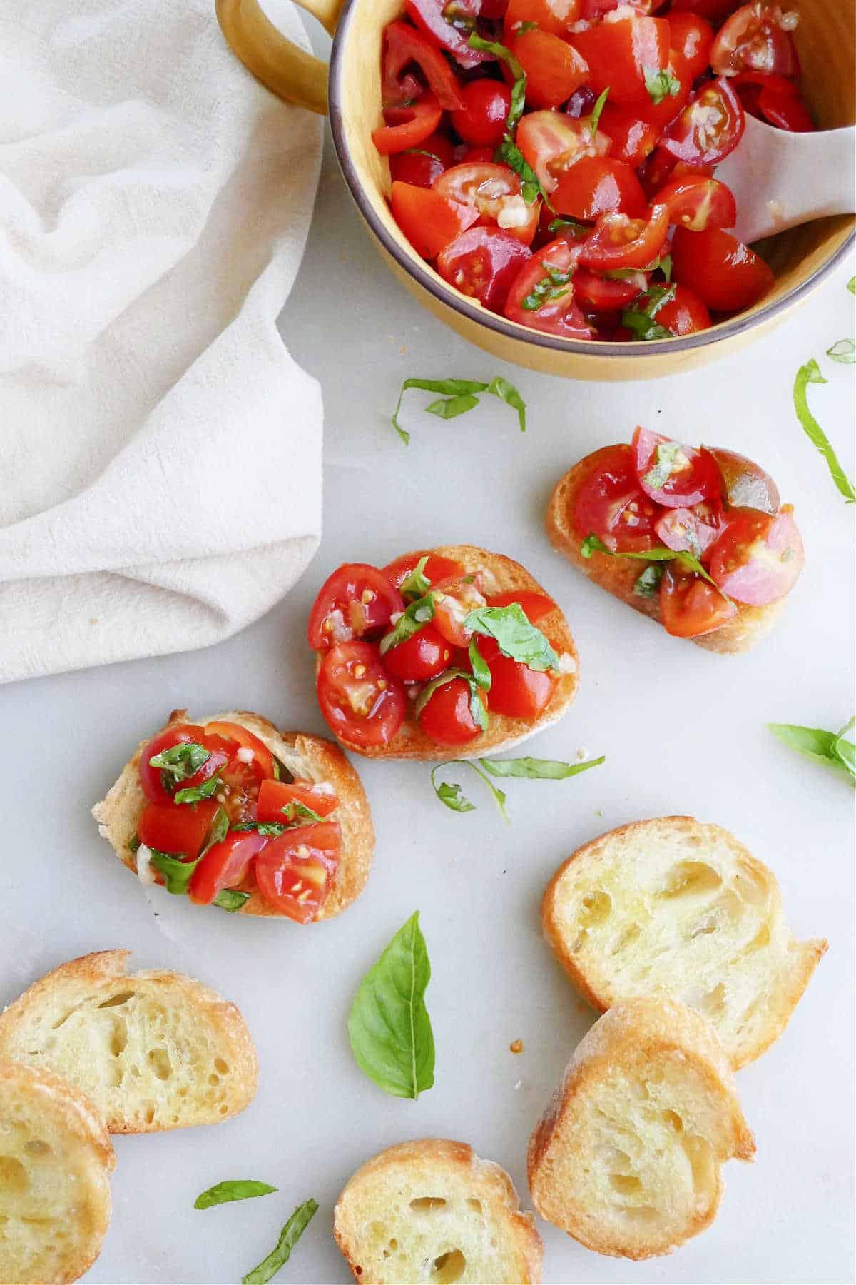 three cherry tomato bruschetta slices next to plain bread slices and topping