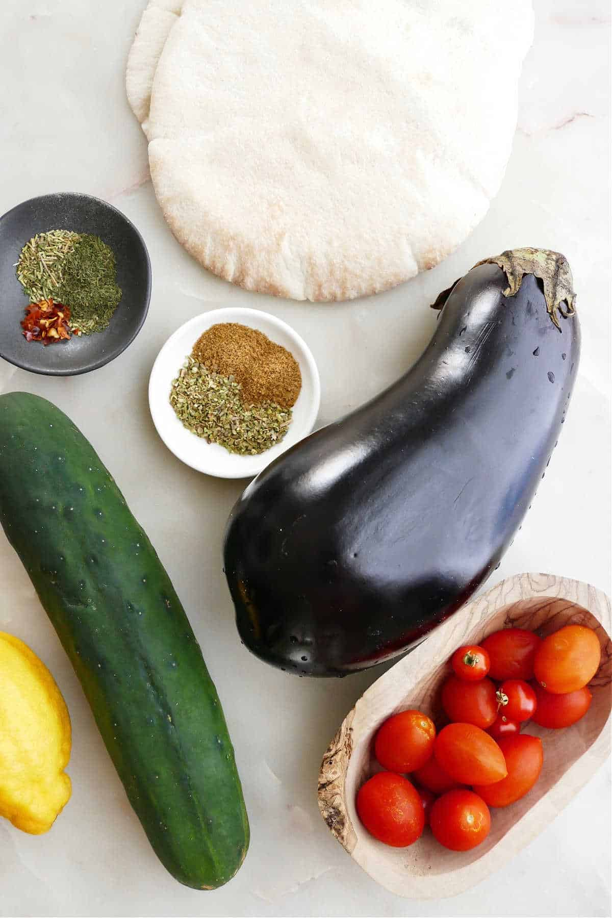 ingredients for eggplant gyro sandwiches spread out next to each other on a counter